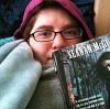bowloffoxtrot: Gray, a paleskinned nonbinary person with glasses, wrapped in several blankets, wearing a hoodie, and holding up a book. (bookish)