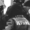 asfreeasleaves: A person wearing a denim jacket. On the back of their jacket is the word defiance. (Default)