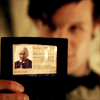 fera_festiva: The eleventh doctor holding up an ID card showing the face of the first doctor (dw: ID card)