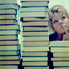 thesisorbust: woman sitting behind a giant stack of books (gen - so many books so little time)