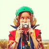 kidjoy: Live version of the girl holding an old camera in front of her face and wearing her full costume ([The Girl])