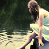 anaraine: A girl sitting on the edge of a dock dipping her foot into the water to create ripples. ([photo] ripple in the water)