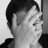 bansidhe: Black and white image of a female obscuring her face with her palm. (Default)