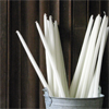 kate: Bunch of white tapers in a bucket against a wooden building (Candle: bucket o white tapers)